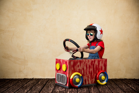 Child driving a car made of cardboard box. Kid having fun at home. Travel and summer vacation concept