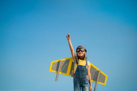 Kid con jet pack finta di essere supereroe. Bambino che gioca in estate all'aperto. Successo, leader e vincitore concetto Archivio Fotografico