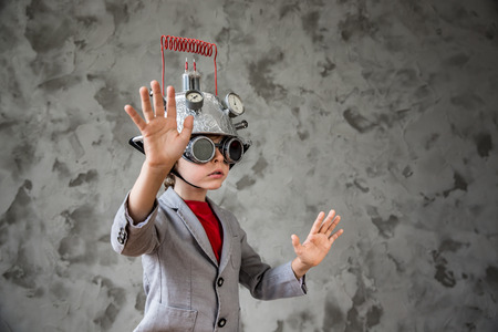 Portrait of young child pretend to be businessman. Kid with toy virtual reality headset in modern loft office. Success, creative and innovation technology concept. Copy space for your text Stock Photo