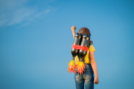 Kid with jet pack pretend to be superhero. Child playing in summer outdoors. Success, leader and winner concept Archivio Fotografico