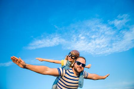 Kid met jet pack doen alsof superheld te zijn. Kind spelen met vader in de zomer. Gelukkig vader en zoon in openlucht. Succes, leider en winnaar begrip