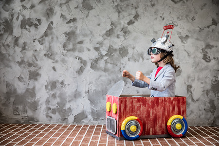 Portrait of young child pretend to be businessman. Kid with toy virtual reality headset in modern loft office. Success, creative and innovation technology concept. Copy space for your text 免版税图像