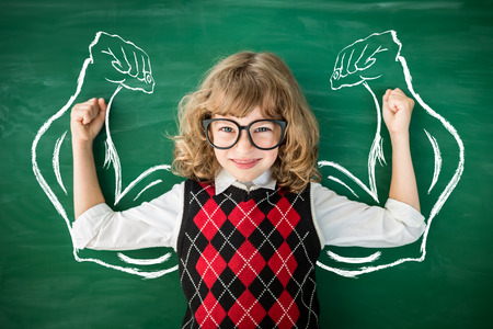 Strong child in class. Funny kid against green blackboard. Knowledge is power concept