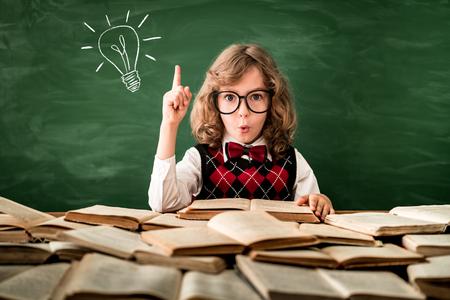 Terug naar school. Schoolkind in de klas. Gelukkig jong geitje tegen groene schoolbord. Onderwijs en creativiteit concept