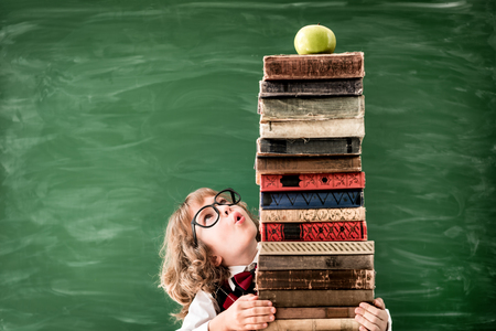 Back to school. Schoolchild in class. Happy kid against green blackboard. Education and creativity concept Stock Photo
