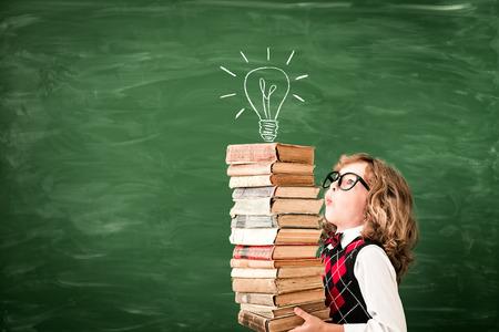 schoolchild: Back to school. Schoolchild in class. Happy kid against green blackboard. Education and creativity concept Stock Photo