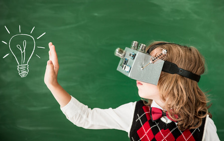 Back to school. Schoolchild with virtual reality headset in class. Funny kid against green blackboard. New idea and creativity concept