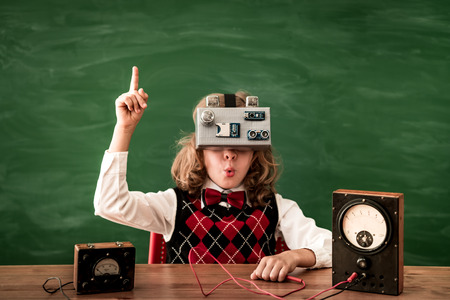 schoolchild: Back to school. Schoolchild with virtual reality headset in class. Funny kid against green blackboard. Innovation and creativity concept Stock Photo