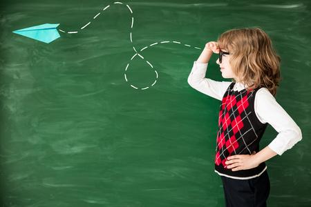 学校に戻る小学生クラスで。グリーン黒板に対して満足の子供。教育と創造性の概念