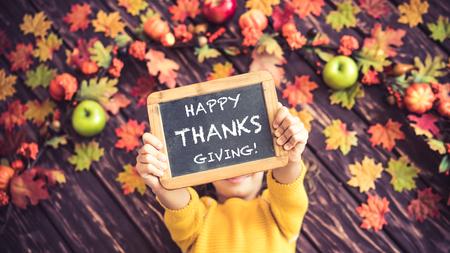 幸せな子秋葉の上に横たわる。面白い子供自宅の平面図の肖像画。感謝祭の休日の概念 写真素材