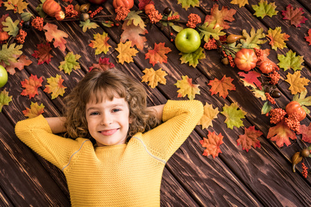 autumn food: Happy child lying on autumn leaves. Top view portrait of funny kid at home. Thanksgiving holiday concept Stock Photo
