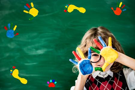 Schoolkind in de klas. Gelukkig kind tegen groene schoolbord. Onderwijs concept Stockfoto