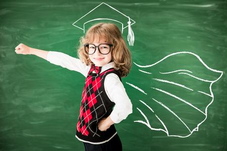 Superhero school child in class. Happy kid against green blackboard. Knowledge is power concept Archivio Fotografico