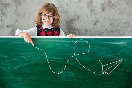 niño escuela: niño en edad escolar en la clase. niño feliz contra la pizarra verde. concepto de estrategia de educación Foto de archivo