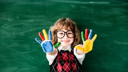 School child in class. Happy kid against green blackboard. Education concept