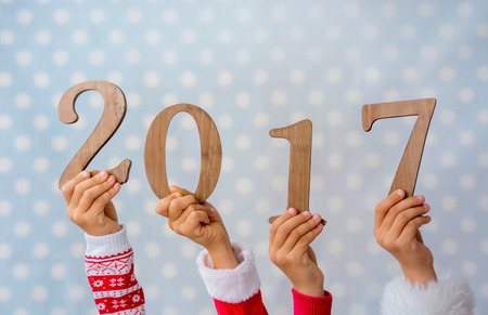 New year holidays concept. Wooden numbers 2017 in children hands against blue background Stock Photo