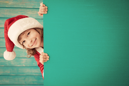 new baby: Child holding banner. Kid hiding behind card blank. Christmas Xmas winter holiday concept Stock Photo