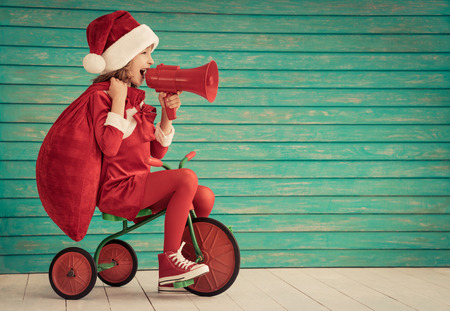 christmas present: Happy child rides a bike. Kid playing at home. Christmas Xmas winter holiday concept