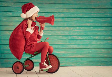 niños en bicicleta: Niño feliz que monta una bicicleta. Niño jugando en casa. concepto de vacaciones de invierno de Navidad