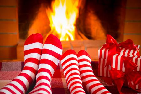 camino natale: Famiglia in Natale calze vicino al camino. Madre; padre e bambino divertirsi insieme. Le persone di relax a casa. Vacanze invernali Natale e concetto nuovo anno