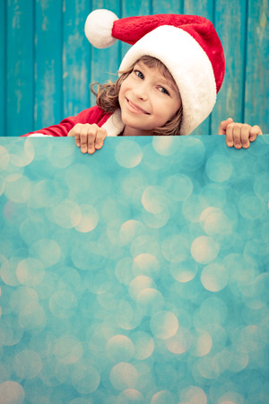 Child holding empty banner. Kid hiding behind card blank. Christmas Xmas winter holiday concept Stock Photo