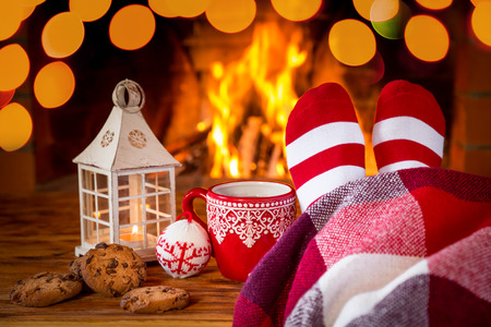 comfort food: Woman in Christmas socks near fireplace. Person relaxing at home. Winter holiday Xmas and New Year concept