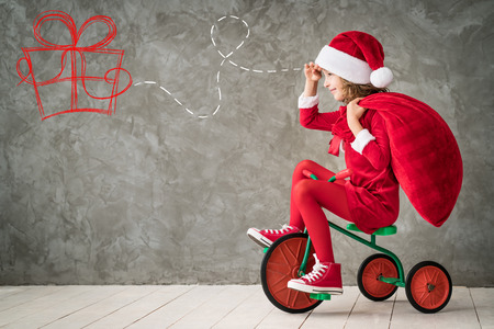 happy christmas: Happy child rides a bike. Kid playing at home. Christmas Xmas winter holiday concept