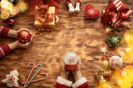 holding a christmas ornament: Christmas tree decorations on wooden table. Children hands holding Xmas ornament. Winter holiday concept Stock Photo