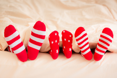 Family in Christmas socks lying on bed. Mother, father and baby having fun together. People relaxing at home. Winter holiday Xmas and New Year concept Standard-Bild