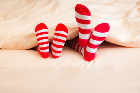 Family in Christmas socks lying on bed. Mother and baby having fun together. People relaxing at home. Winter holiday Xmas and New Year concept
