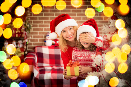 surprised kid: Surprised kid with Christmas gift. Mother and child having fun together. People playing at home. Winter holiday Xmas and New Year concept
