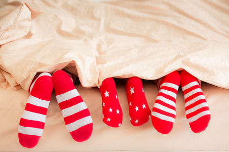 Family in Christmas socks lying on bed. Mother, father and baby having fun together. People relaxing at home. Winter holiday Xmas and New Year concept 版權商用圖片