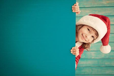 Kind bedrijf banner. Kid verschuilen achter kaart leeg. Kerstmis Xmas winter vakantie concept Stockfoto
