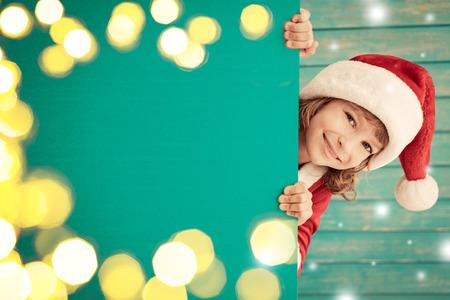 sorpresa: Niño que sostiene la bandera. Kid oculta detrás de la tarjeta en blanco. concepto de vacaciones de invierno de Navidad