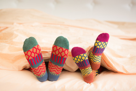 woman foot: Couple in Christmas socks in bedroom. Man and woman lying on bed. People relaxing at home. Winter holiday Xmas and New Year concept