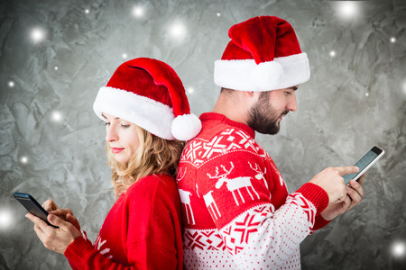 red hat: Portrait of funny couple with smartphones. Man and woman having fun together. Winter holiday Christmas and New Year concept