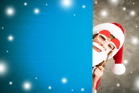 1: Child holding banner. Kid hiding behind card blank. Christmas Xmas winter holiday concept Stock Photo