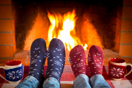 woman foot: Family in Christmas socks near fireplace. Mother; father and baby having fun together. People relaxing at home. Winter holiday Valentine Day concept Stock Photo