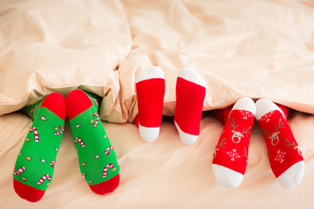men socks: Family in Christmas socks lying on bed. Mother, father and baby having fun together. People relaxing at home. Winter holiday Xmas and New Year concept Stock Photo