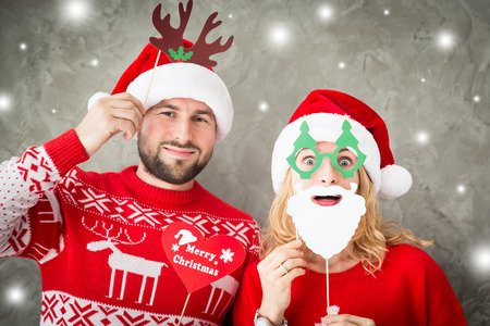 Portrait of funny couple with Christmas paper props. Man and woman having fun together. Winter holiday Xmas and New Year concept Stock Photo