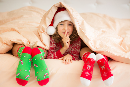 men socks: Family in Christmas socks lying on bed. Mother, father and child having fun together. People relaxing at home. Winter holiday Xmas and New Year concept Stock Photo