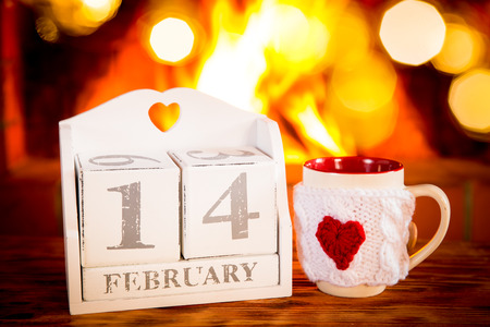 14 february: Calendar 14 February and cup near fireplace. Valentines day holiday concept