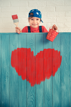 Happy child painting big red heart on the wall. Funny girl playing at home. Valentines day card. Renovation and design concept Reklamní fotografie