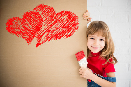 Happy child painting big red heart on the wall. Funny girl playing at home. Valentines day card. Renovation and design concept Stock Photo