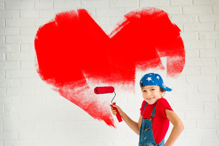 painting: Happy child painting big red heart on the wall. Funny girl playing at home. Valentines day card. Renovation and design concept Stock Photo