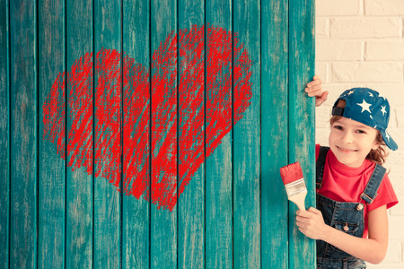 Happy child painting big red heart on the wall. Funny girl playing at home. Valentines day card. Renovation and design concept Stok Fotoğraf
