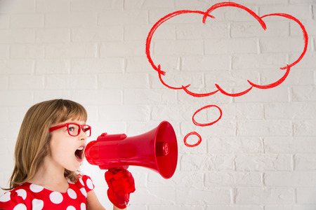 Child girl shouting by retro megaphone. Valentines day concept