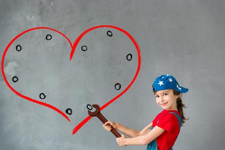 niños felices: Niño feliz que sostiene la llave grande de color rojo. Mano corazón dibujado en la pared. chica divertida que juega en casa. Tarjetas de San Valentín. Renovación y diseño de concepto Foto de archivo