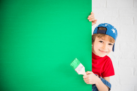 Happy child holding banner blank. Kid playing at home. Spring renovation and design concept Stock Photo