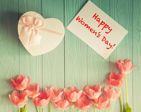 木製テーブルの上のチューリップの平面図です。女性の日。3 月 8 日。春の休日の概念
